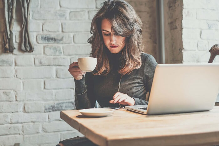 コーヒーを飲みながらスマホをいじる女性
