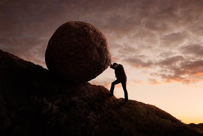岩を転がす男性