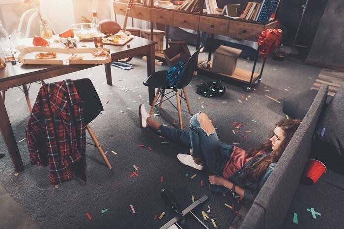 汚い部屋に寝転ぶ女性