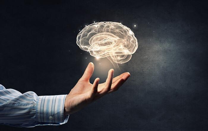 宙に浮かぶ脳と男性の手