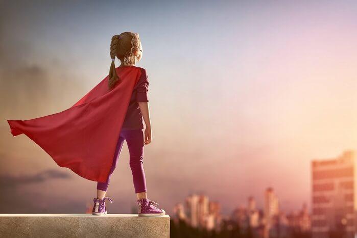 ビルの上に立つ子どものスーパーマン