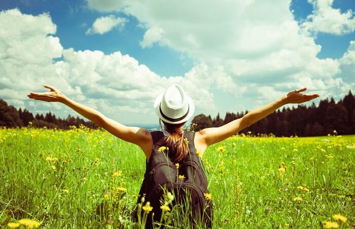 草原で両手を広げる女性