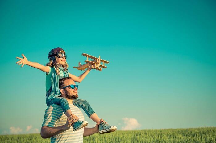 肩車をして飛行機を飛ばそうとしている親子