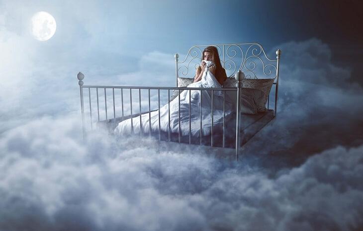 雲の上にあるベッドで怯える女性