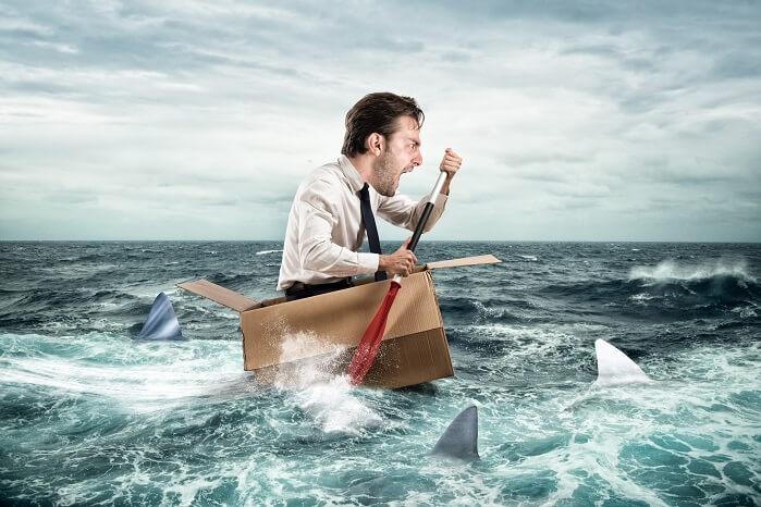 ダンボールの船に乗ってサメから逃げる男性