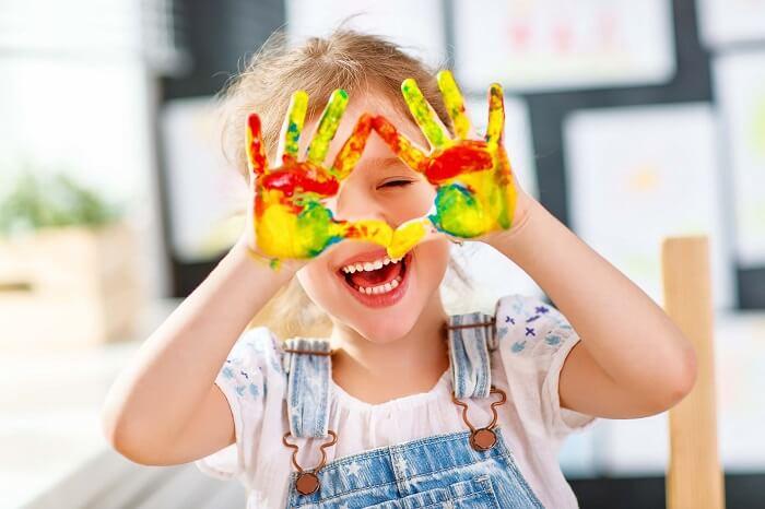 沢山の絵の具を手につけて笑う女の子