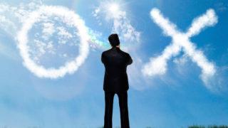 空に浮かぶ◯と×を眺めるビジネスマン