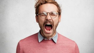 Emotional mad crazy young male screams loudly and with anger, being stressed and in panic, frowns face, isolated over white concrete wall. Negative human emotions, feelings, reaction concept
