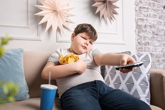 お菓子を食べながらテレビをつける男の子