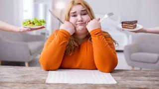 ケーキとサラダのどちらを食べるか迷う女性