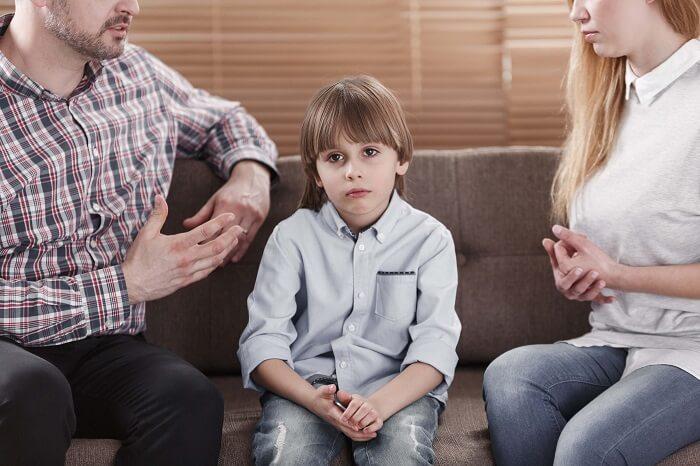 遠くをぼんやり見つめる子供と大人二人