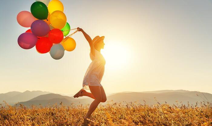 風船を持ってジャンプする女性