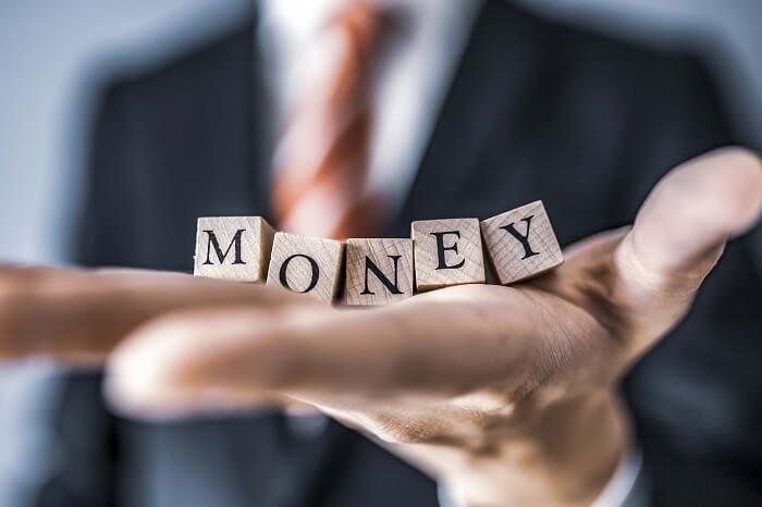 MONEYと書かれた積み木を持つビジネスマン