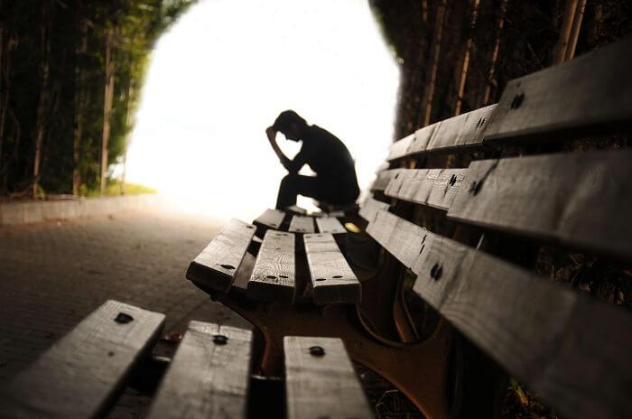 ベンチに座って落ち込む男性