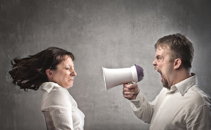 メガホンで叫ぶ男性と怒鳴られる女性