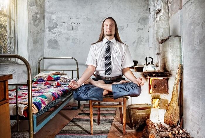 汚い部屋で瞑想する男性