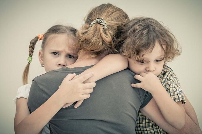 大人に抱きつく二人の子ども