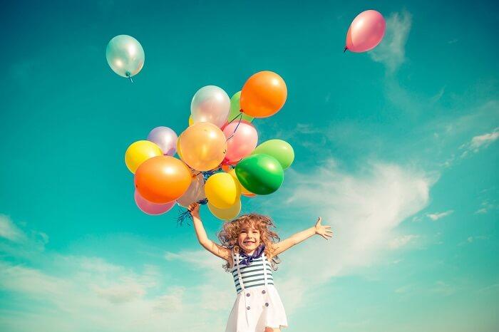 沢山の風船を持って笑う子ども