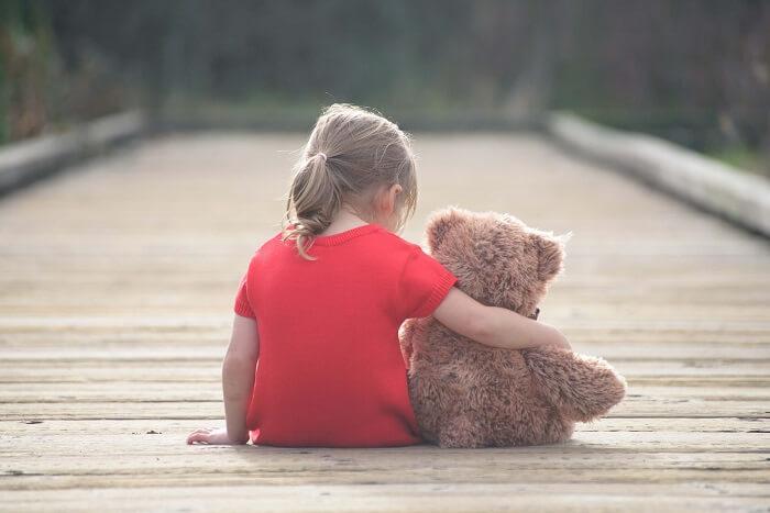 クマのぬいぐるみを持って座っている女の子