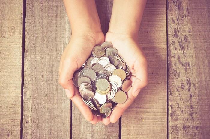 小銭を手のひらいっぱいにもっている画像