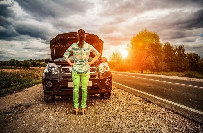 故障した車を眺める女性