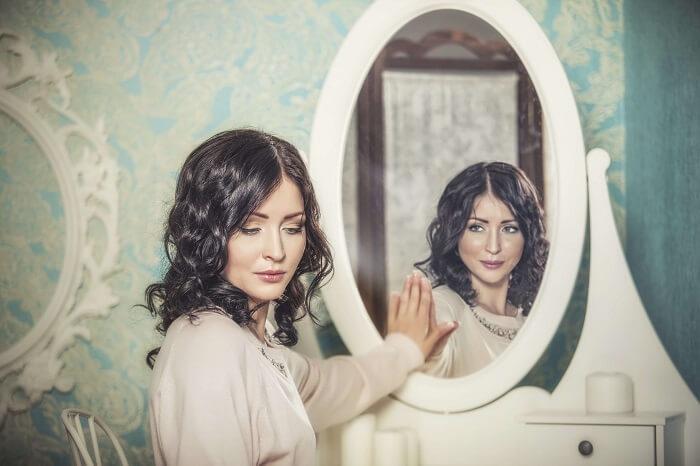 鏡に手を置いて目をそらす女性