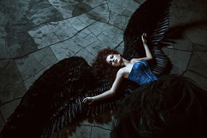 黒い羽がある倒れた女性