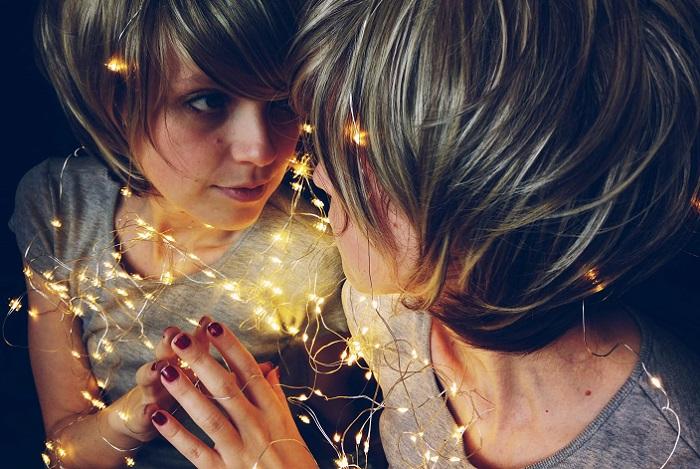 鏡の自分を見つめる女性