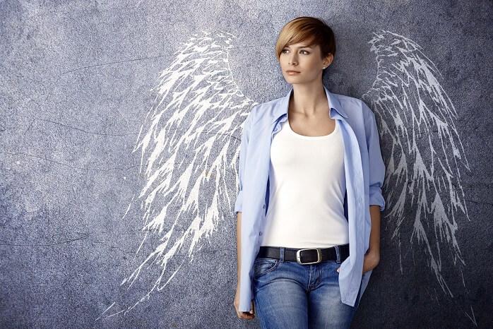天使のはねが書かれた黒板の前に立つ女性